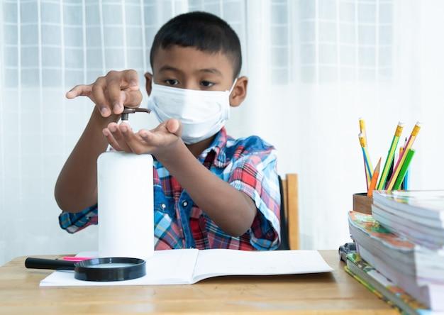 Piccola mano asiatica sveglia del lavaggio del ragazzo con il prodotto disinfettante Foto Premium