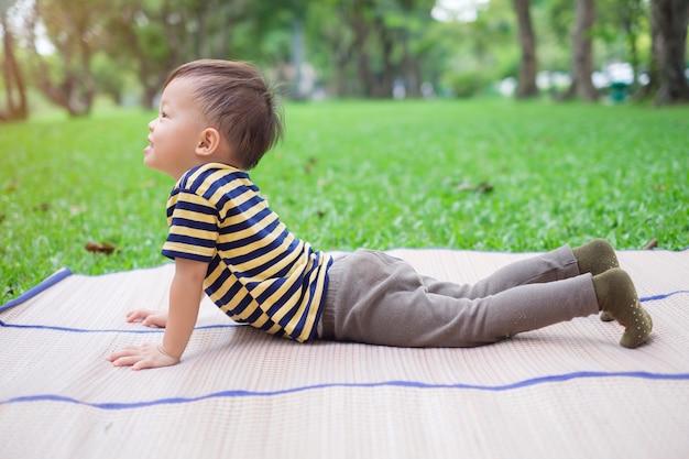 Il piccolo bambino asiatico sveglio del ragazzo del bambino pratica l'yoga nella posa della cobra e meditare all'aperto sulla natura nell'ora legale, concetto sano di stile di vita Foto Premium