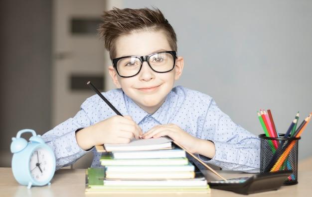 Ragazzino sveglio che fa i compiti. scuola del nemico di apprendimento del bambino. Foto Premium