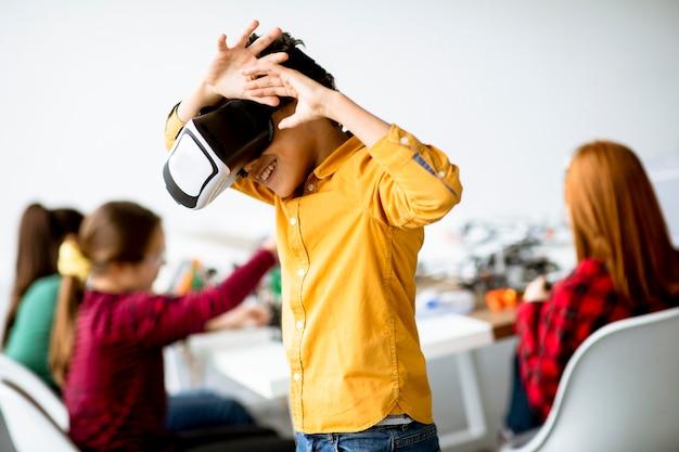 Ragazzino sveglio che indossa occhiali per realtà virtuale vr in un'aula di robotica Foto Premium