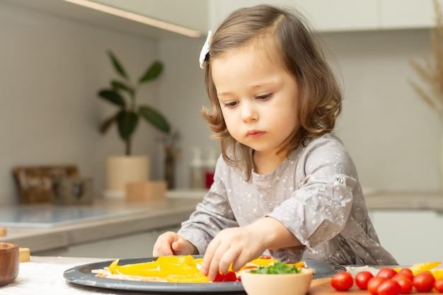 Bambina sveglia 2-4 in vestito grigio che cucina la pizza in cucina. il bambino organizza gli ingredienti sulla base della pizza Foto Premium