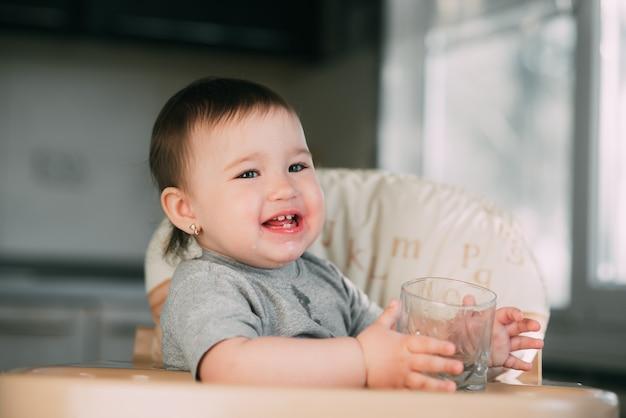 Bambina sveglia che si siede su un seggiolone in cucina e acqua potabile Foto Premium