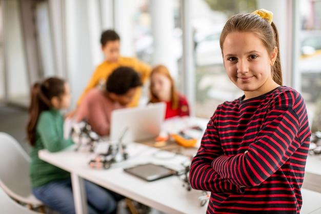 Bambina sveglia che sta davanti a un gruppo di bambini che programmano giocattoli elettrici e robot all'aula di robotica Foto Premium