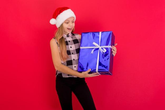 Bambina sveglia che indossa il cappello di natale in piedi isolato su sfondo rosso, tenendo presente la casella blu Foto Premium