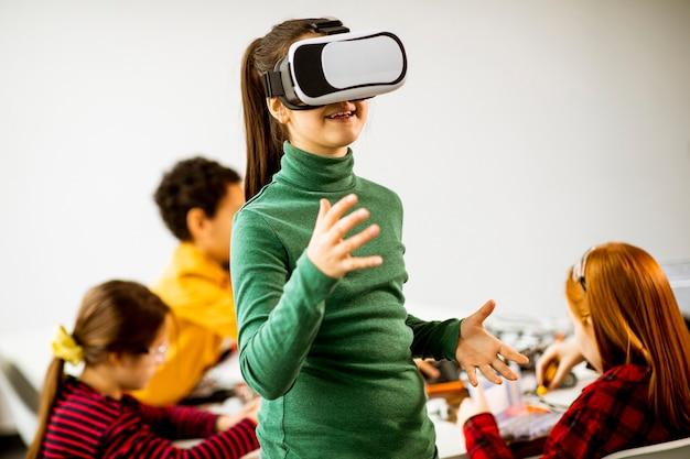 Bambina sveglia che indossa occhiali per realtà virtuale vr in un'aula di robotica Foto Premium
