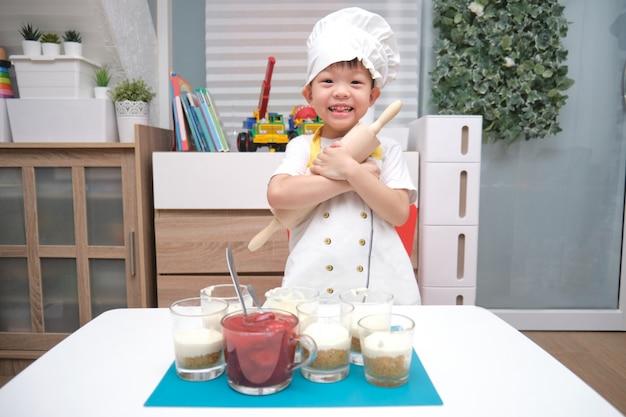 Asiatici sorridenti svegli 4 anni del bambino del ragazzo con un matterello divertendosi cucinando il dolce della fragola a casa, attività dell'interno di divertimento per il concetto di asilo Foto Premium