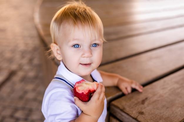Piccola scolara sorridente sveglia che tiene un hamburger e succo d'arancia all'aperto Foto Premium