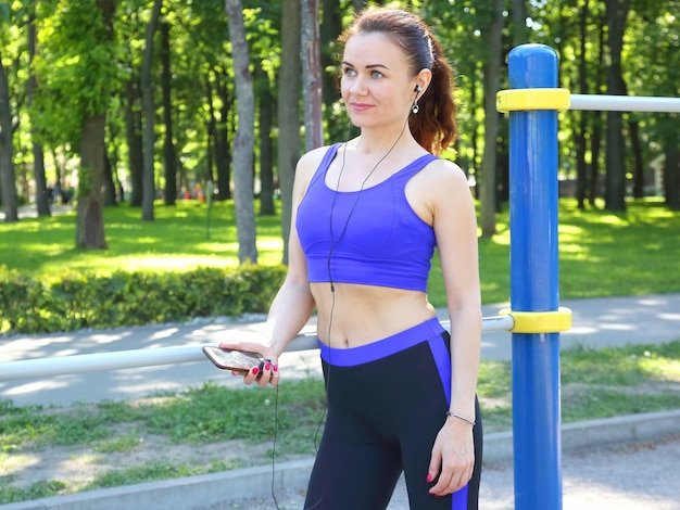 Carina giovane donna sportiva che ascolta la musica in una passeggiata Foto Premium