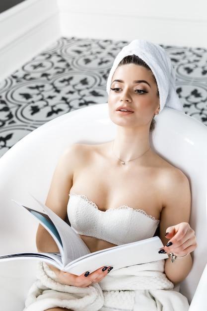 Carina giovane donna con un asciugamano in testa si siede in bagno e legge una rivista Foto Premium