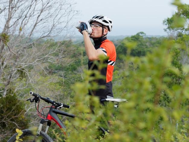 Acqua potabile del ciclista dalla bottiglia di acqua sulla cima di una montagna con vista sull'oceano. l'uomo in un casco bianco con una bicicletta beve acqua. mountain bike. Foto Premium