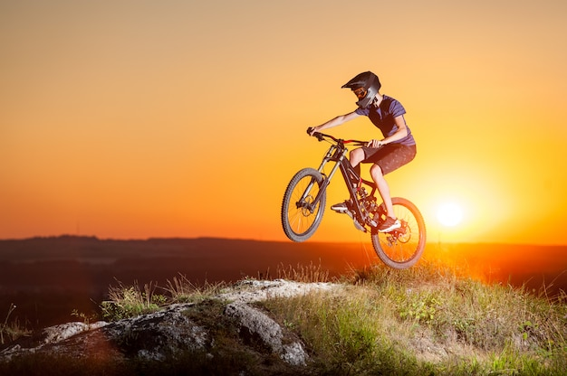 Ciclista che guida in discesa sulla mountain bike sulla collina Foto Premium
