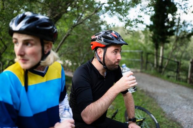 Ciclisti che riposano e acqua potabile nella foresta Foto Premium