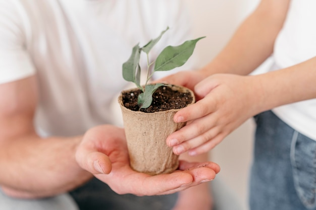 Papà e figlio che tengono il vaso della pianta Foto Premium