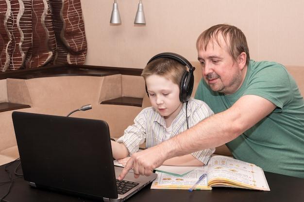 Papà e figlio guardano un video di e-learning nel soggiorno di casa. Foto Premium