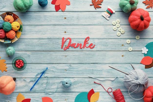 Danke significa grazie in tedesco. cornice decorativa composta da fasci di lana, gomitoli di filato, zucche decorative in feltro Foto Premium