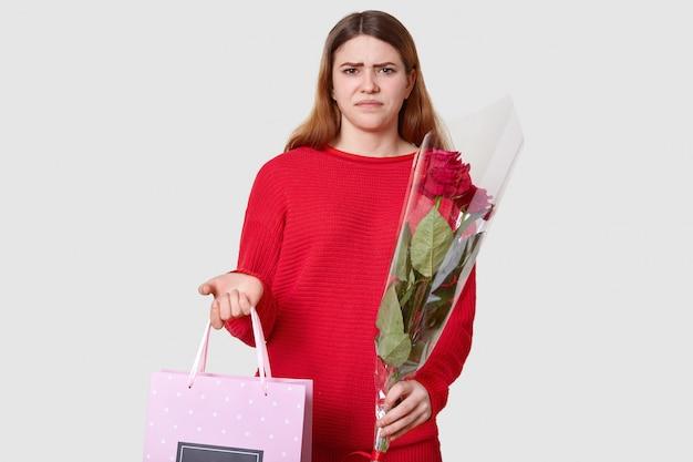 La donna insoddisfatta dai capelli scuri aggrotta le sopracciglia, non gli piace il presente, tiene il sacchetto regalo in una mano e il mazzo di fiori nell'altra, isolato su bianco, indossa un maglione casual rosso. non mi piace Foto Premium