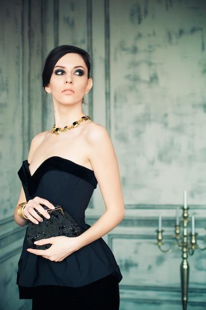 Donna dai capelli scuri in elegante abito nero con borsetta in piedi all'interno della stanza con candelabri. Foto Premium