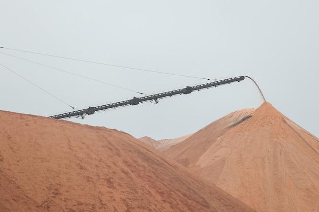 Montagne giallo scuro di discariche di sale in cima alle quali c'è una macchina per l'estrazione del sale Foto Premium