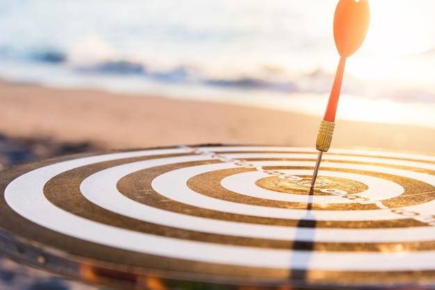 Il centro del colpo della freccia del dardo su bullseye di un bersaglio è l'obiettivo del business della sfida Foto Premium