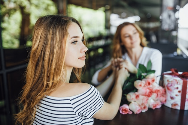 La figlia presenta un regalo e un mazzo di rose in un caffè con terrazza estiva in abiti casual. Foto Premium
