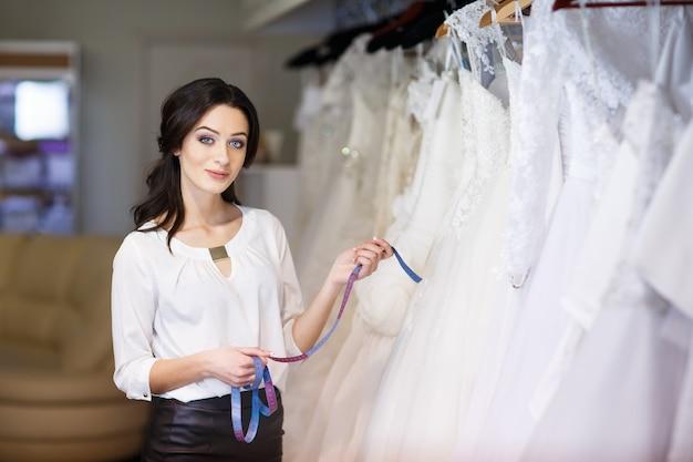 Consulente del rivenditore sullo sfondo di abiti da sposa Foto Premium