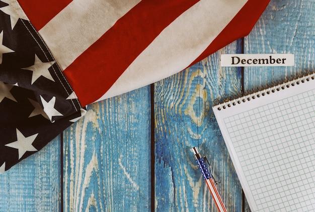 Mese di dicembre dell'anno civile bandiera degli stati uniti d'america del simbolo di libertà e democrazia con il blocco note e la penna in bianco sulla tavola di legno dell'ufficio Foto Premium