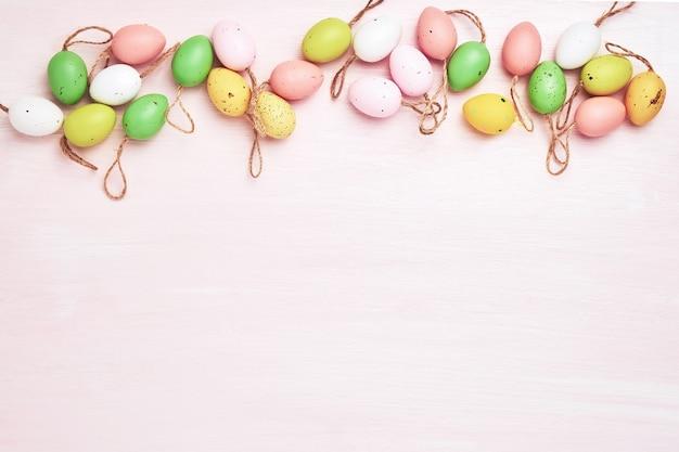 Uova di pasqua colorate decorative su fondo di legno rosa. copia spazio, vista dall'alto, tonica Foto Premium