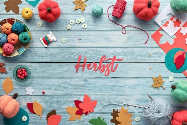 Cornice decorativa composta da fasci di lana, gomitoli di lana, zucche decorative in feltro e foglie autunnali colorate. testo cartaceo herbst Foto Premium