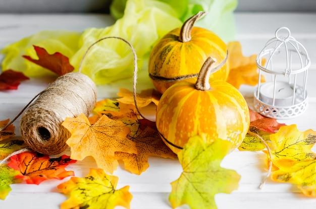 Mini zucche decorative con foglie secche cadono, candela su sfondo scuro, Foto Premium