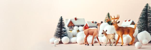Famiglia di cervi alla vigilia di natale sullo sfondo di case rurali, mockup di natale Foto Premium
