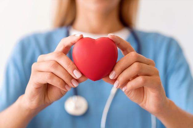 Medico femminile defocused che tiene forma del cuore Foto Premium