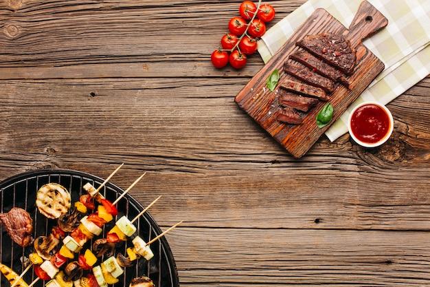 Deliziosa carne fritta e grigliata con salsa su legno strutturato Foto Premium