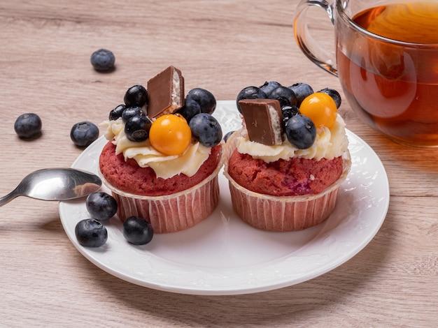 Deliziosi muffin alla frutta con frutti di bosco e cioccolato su un piatto bianco e una tazza rotonda di tè. colazione fatta in casa su un tavolo di legno. Foto Premium