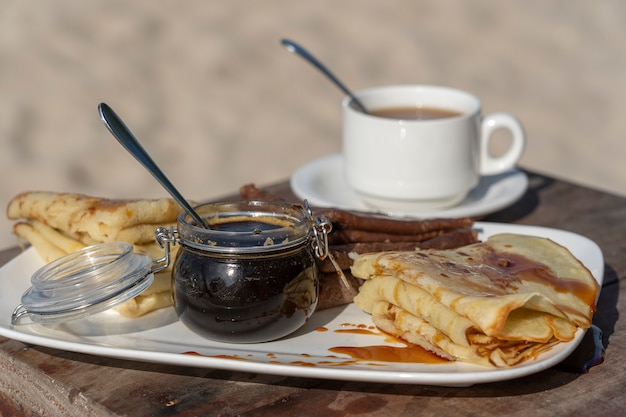 Pancake deliziosi con il miele della mangrovia e la tazza bianca di tè sulla tavola, fine su Foto Premium