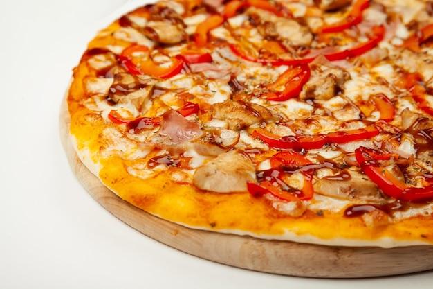 Deliziosa pizza con pancetta e pollo teriyaki servita su un piatto di legno, ingredienti salsa firma, mozzarella, pollo teriyaki, pancetta, pepe bulgaro, salsa teriyaki su bianco. Foto Premium