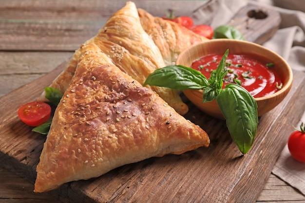 Delizioso samsa con carne di pollo e salsa sul tavolo di legno Foto Premium