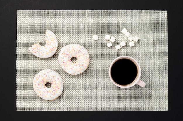 Ciambelle deliziose, dolci, fresche, una tazza di caffè, sfondo nero. concetto di colazione, fast food, caffetteria, panetteria, pranzo. vista piana, vista dall'alto. Foto Premium