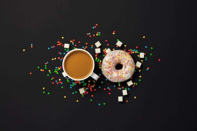 Ciambelle deliziose, dolci, fresche, caramelle decorative multicolori, una tazza di caffè su sfondo nero. concetto di colazione, fast food, caffetteria, prodotti da forno. vista piana, vista dall'alto. Foto Premium