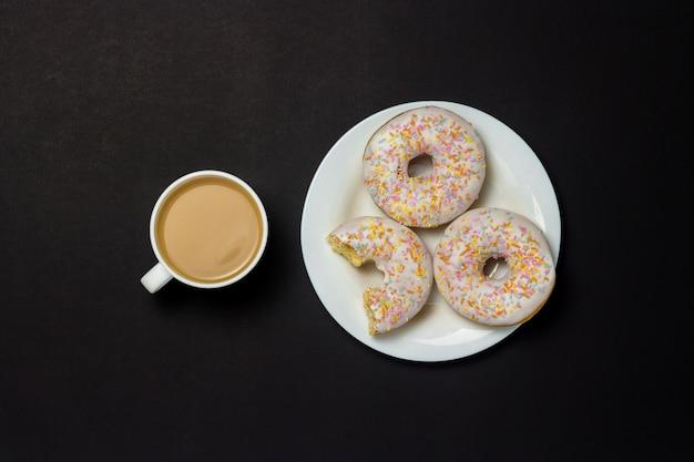 Ciambelle deliziose, dolci, fresche su un piatto bianco, una tazza di caffè, fondo nero. concetto di colazione, fast food, caffetteria, prodotti da forno. vista piana, vista dall'alto. Foto Premium
