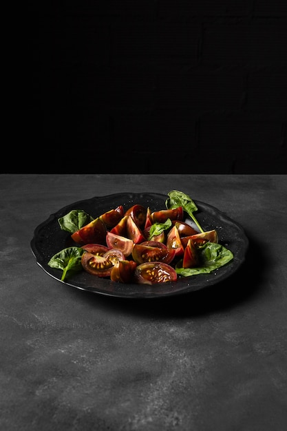 Deliziosa insalata di pomodori copia spazio sfondo nero Foto Premium