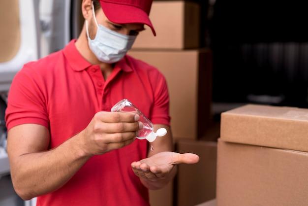 Maschio di consegna con disinfettante per le mani Foto Premium