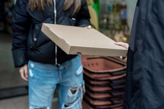 Uomo di consegna che consegna cibo ai clienti a casa, tenendo in mano un sacchetto rosso Foto Premium