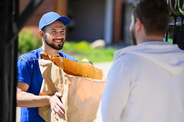 Uomo di consegna felice di distribuire generi alimentari al cliente Foto Premium
