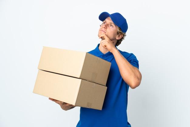 Uomo di consegna su bianco isolato che ha dubbi Foto Premium