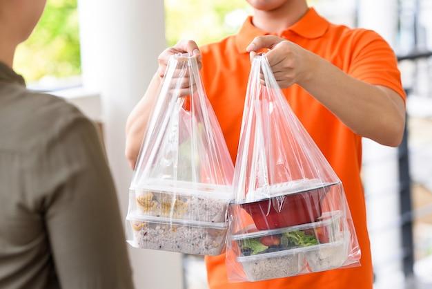 Fattorino in uniforme arancio che consegna le scatole di alimento asiatiche in sacchetti di plastica ad un cliente della donna a casa Foto Premium
