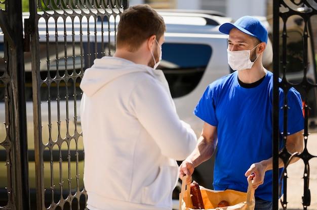 Uomo di consegna con maschera che distribuisce generi alimentari Foto Premium