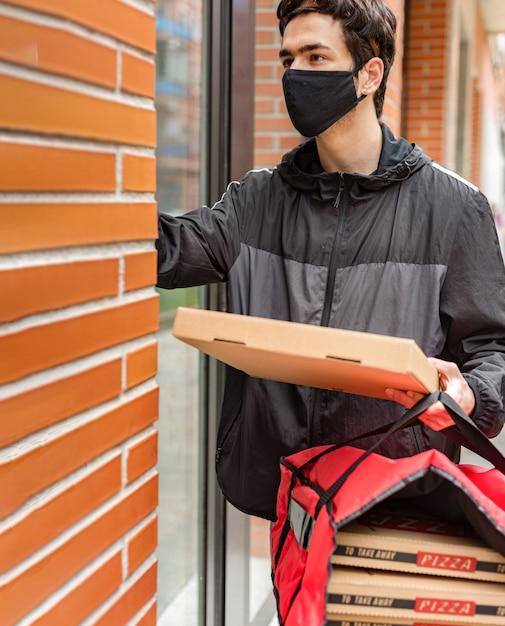 Fattorino con la maschera sul viso che chiama il portiere, con in mano un sacchetto rosso per la consegna a domicilio Foto Premium