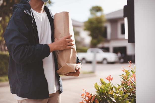 Fattorino con maschera protettiva consegnare generi alimentari e cibo in un sacchetto di carta riutilizzabile da vicino con copyspace Foto Premium