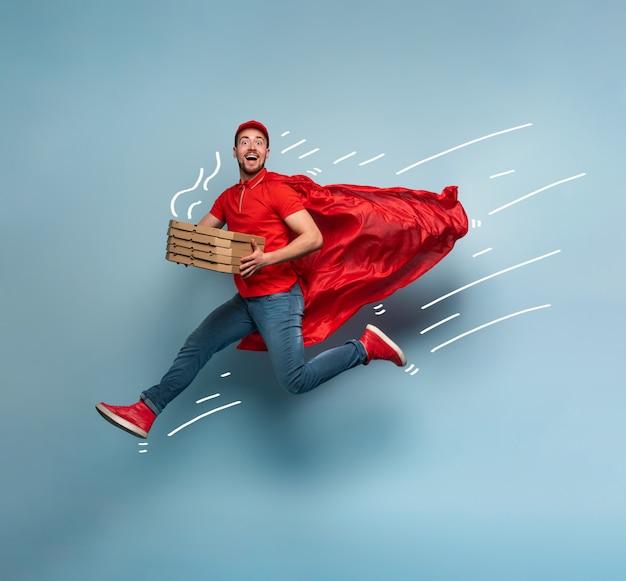 Il fattorino con le pizze si comporta come un supereroe potente. concetto di successo e garanzia sulla spedizione. studio sfondo ciano Foto Premium