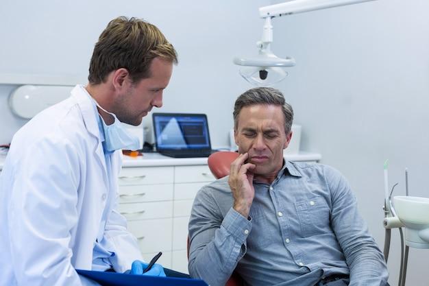 Dentista che esamina un paziente maschio Foto Premium